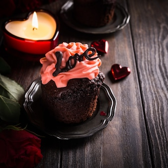 Beautiful chocolate cupcake with pink cream on wooden surface. valentines, mother day, wedding greeting card. dark photo. copy space