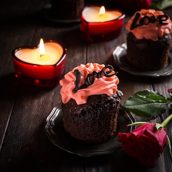 Beautiful chocolate cupcake with pink cream on wooden surface. valentines, mother day, wedding greeting card. dark photo