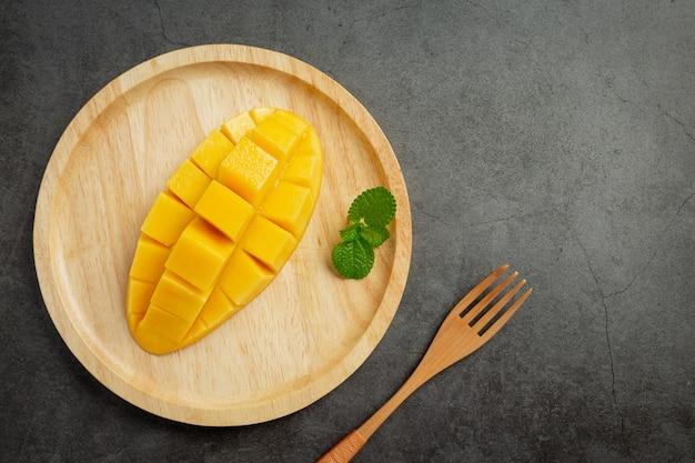 Beautiful chopped ripe mango on dark wooden surface