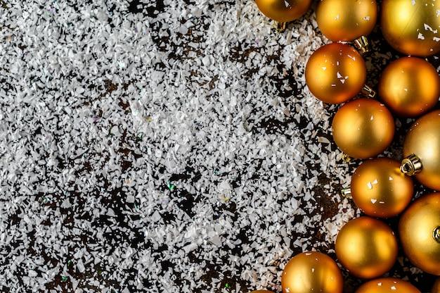 暗い黒の背景に白い雪の美しいクリスマスと新年のゴールデンデコつまらない。フラットレイアウトデザイン。コピースペース