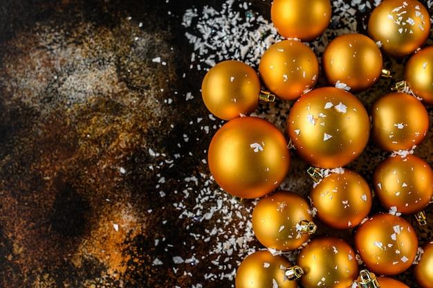暗い黒の背景に白い雪の美しいクリスマスと新年の黄金のデコつまらない