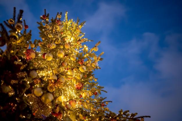 Красивый новогодний фон. вид снизу на красивую высокую елку, украшенную шарами и светящимися гирляндами, на фоне голубого вечернего неба
