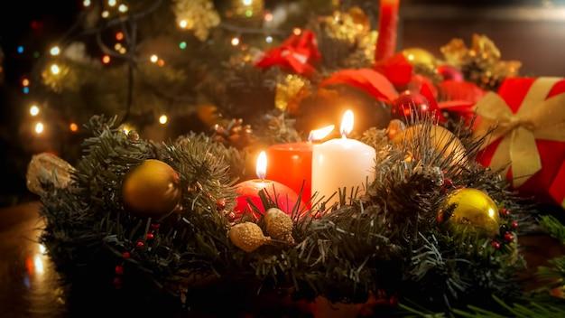 Красивый новогодний фон из зажженных свечей, светящихся огней и рождественского венка в гостиной