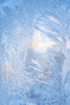 Красивый новогодний фон с синим морозным узором на стекле