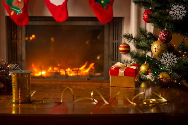 燃える暖炉、クリスマスツリー、ギフトボックス、木製のテーブルと美しいクリスマスの背景