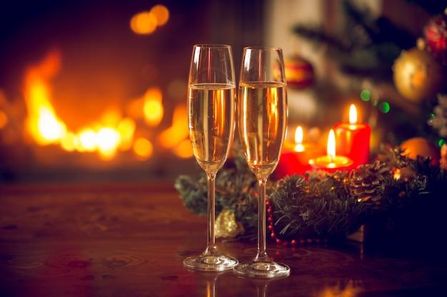 2つのシャンパンフルート、燃える暖炉、キャンドルと花輪の美しいクリスマスの背景。美しいクリスマスの背景