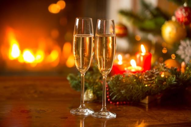 두 개의 샴페인 플루트, 불타는 벽난로, 촛불이 있는 화환이 있는 아름다운 크리스마스 배경