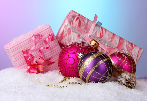 Beautiful christmas balls and gifts on snow on bright background