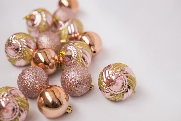 Beautiful christmas balls pink and gold on white surface