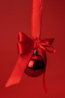 Красивая рождественская безделушка висит на красной атласной ленте на красном фоне