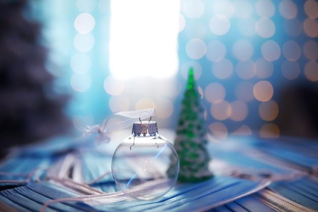 의료 마스크와 어두운 검은 배경에 아름 다운 크리스마스 싸구려. 코로나 바이러스 . 검역에 새 해입니다.평평한 디자인입니다. 복사 공간. 정사각형 형식입니다. 형세.