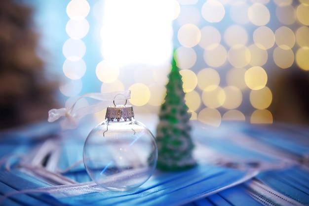 Красивые рождественские безделушки на темном черном фоне с медицинской маской. коронавирус . новый год на карантине. плоская планировка. копировать пространство. квадратный формат. макет.