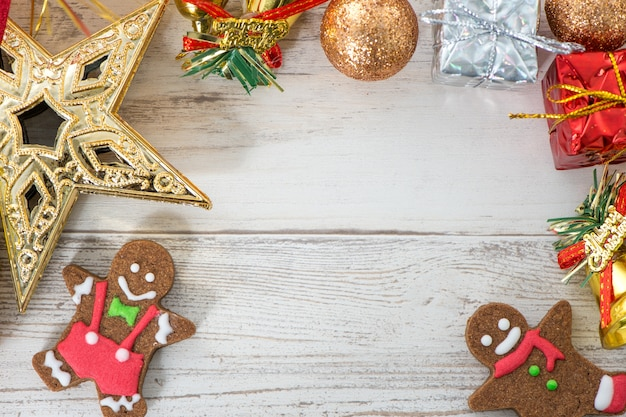 明るい木製の背景に焼きジンジャーブレッドマンクッキーと美しいクリスマスの構成と装飾