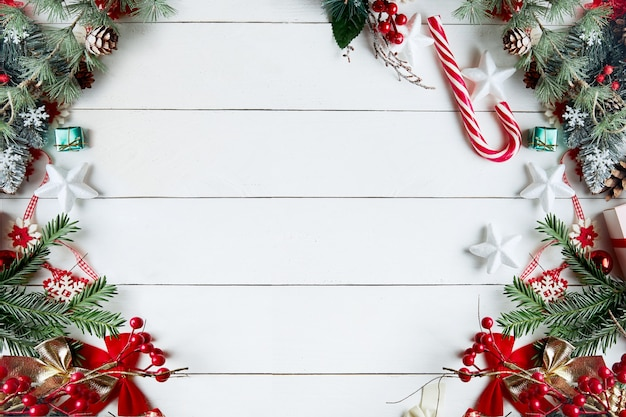 Красивая рождественская композиция на белом фоне с рождественскими подарочными коробками, заснеженными еловыми ветками, хвойными шишками, праздничным украшением, карамельной палочкой и красной ягодой.