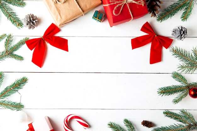 木製の白い背景の上の美しいクリスマスの構成。クリスマスプレゼントボックス、雪に覆われたモミの枝