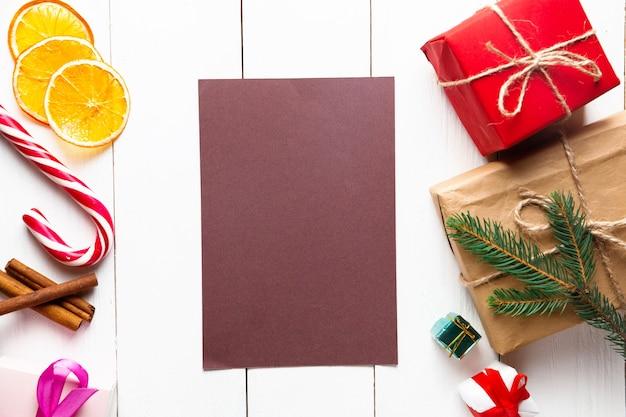 木製の白い背景の上の美しいクリスマスの構成。クリスマスプレゼントボックス付きの空のカード