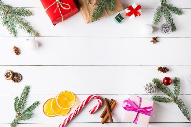 Красивая рождественская композиция на деревянном белом фоне с рождественскими подарочными коробками, сухофруктами, праздничным украшением, карамельной палкой. новый год.