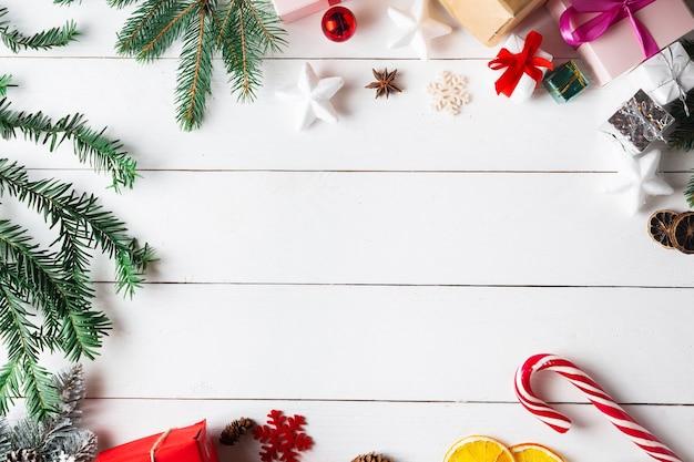 クリスマスギフトボックスと木製の白い背景の上の美しいクリスマスの構成