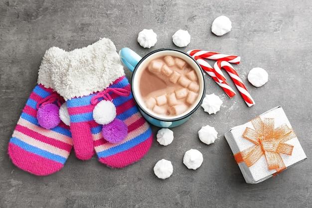 회색 배경에 뜨거운 코코아, 장갑, 선물 상자가 있는 아름다운 크리스마스 구성