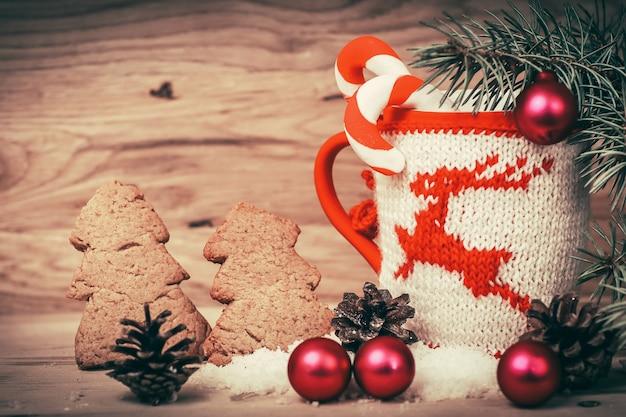 木製のテーブルの上の美しいクリスマスカップとジンジャーブレッドマン。テキストのスペースと写真