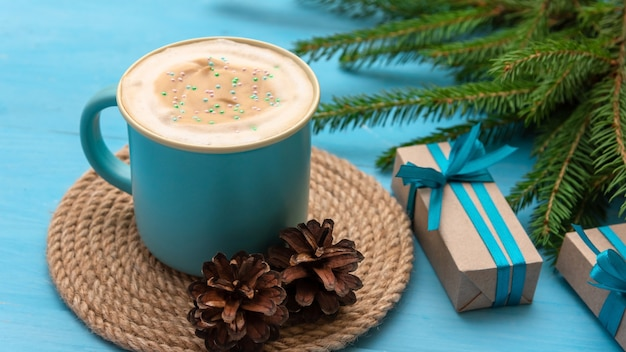 On a beautiful christmas day, there is coffee with foam and gifts on the table.