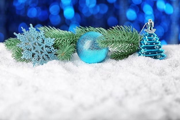 焦点がぼけた光に対して白い雪の上の美しいクリスマスの装飾