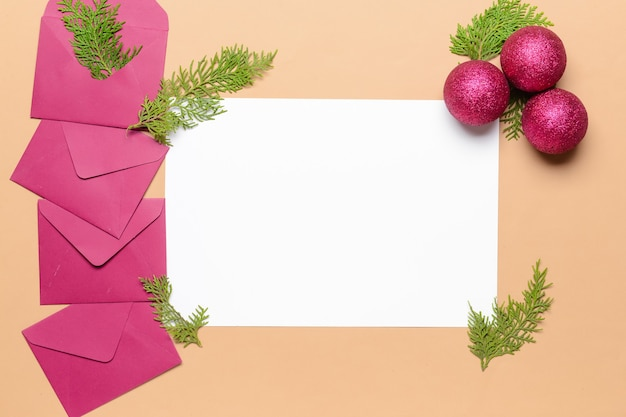 Beautiful christmas decorations with empty card and envelopes on color surface