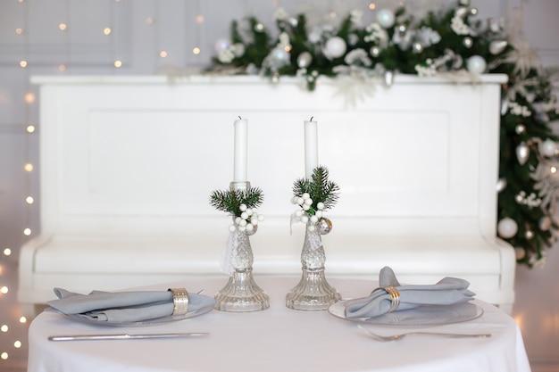 美しいクリスマスディナーの設定。冬の装飾と白いキャンドルの中でテーブルクロスでお祝いテーブルの設定。トップビュー、フラットレイアウト。クリスマスや感謝祭の家族の夕食の概念。