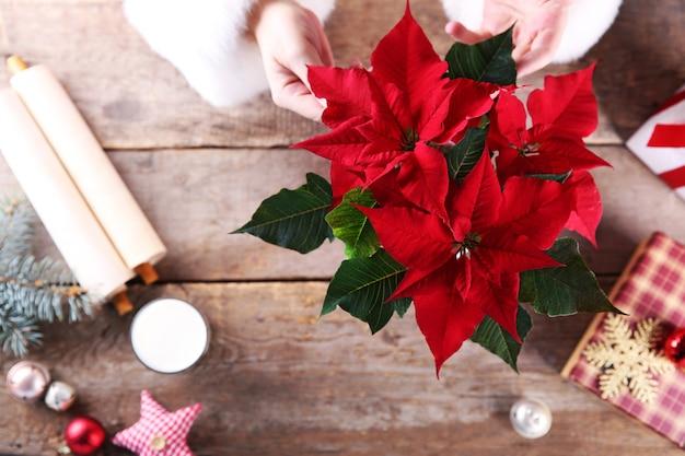 木製のテーブルに他の装飾と美しいクリスマスの花、クローズアップ