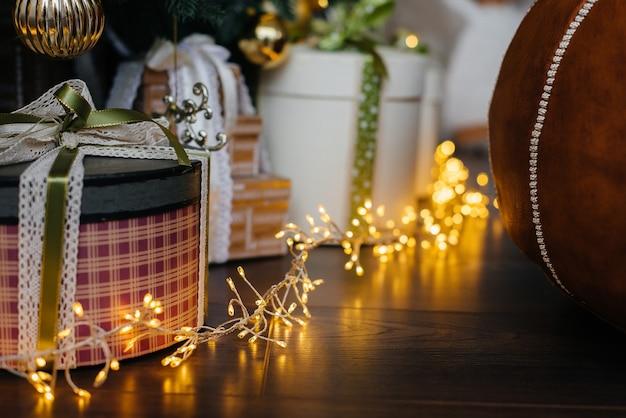 Красивая рождественская гирлянда рядом с рождественскими подарками.