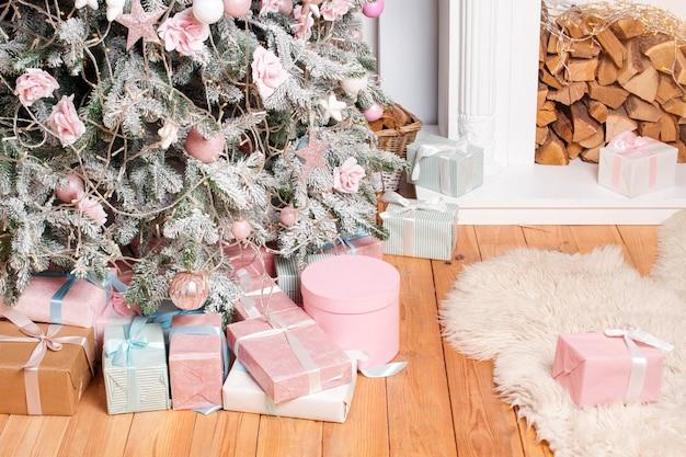 Красивые рождественские подарочные коробки на полу возле елки в комнате с камином, рождественские подарки и украшения, счастливые зимние праздники.