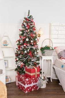 Красивые рождественские подарки под елкой в новогоднем интерьере дома
