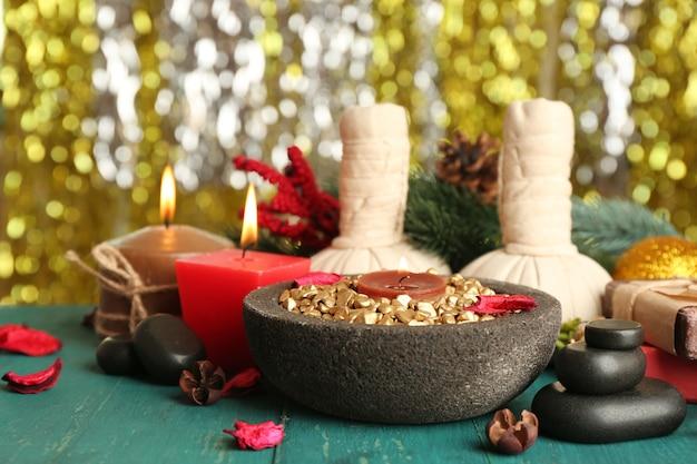 美しいクリスマスは、キラキラ光る背景のクローズアップに対して緑の木製テーブルに構成を提示します
