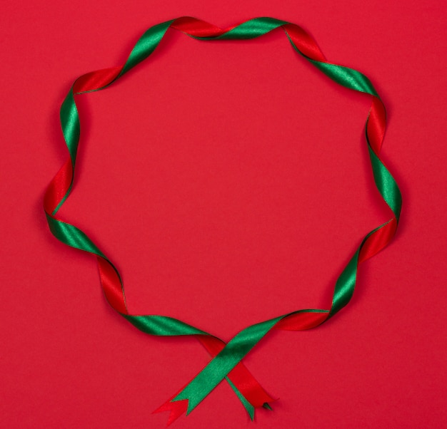 Beautiful christmas round frame of wavy ribbons on red background. festive backdrop for yo
