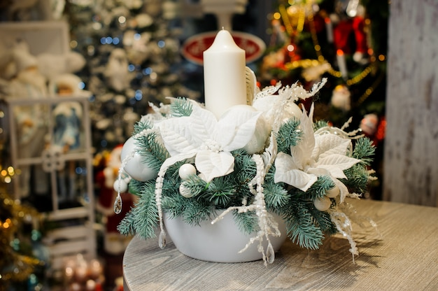 Beautiful christmas table decorative composition with white candle, flowers and fir tree branches in white vase
