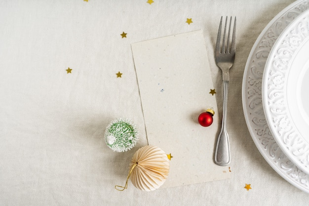 Beautiful christmas table setting with space for menu over white plates with silver cutlery on linen tablecloth background