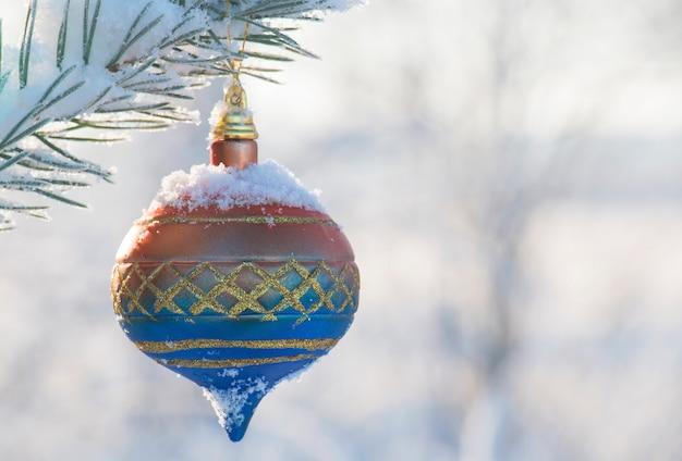 Красивый елочный шар, украшение на заснеженной хвойной ветке в лесу в морозный зимний день