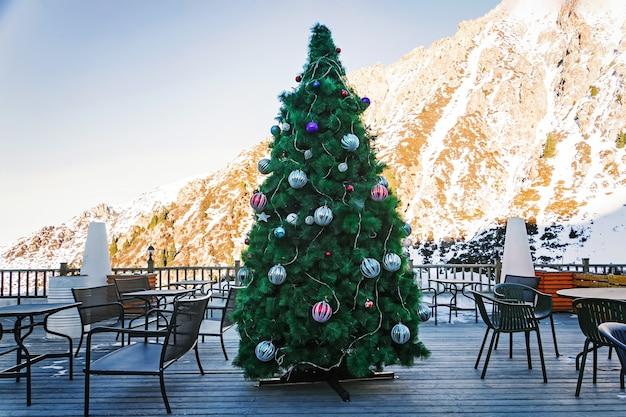 산의 높은 대낮에 야외 카페에서 산 배경에 공과 화환으로 장식된 아름다운 크리스마스 트리.