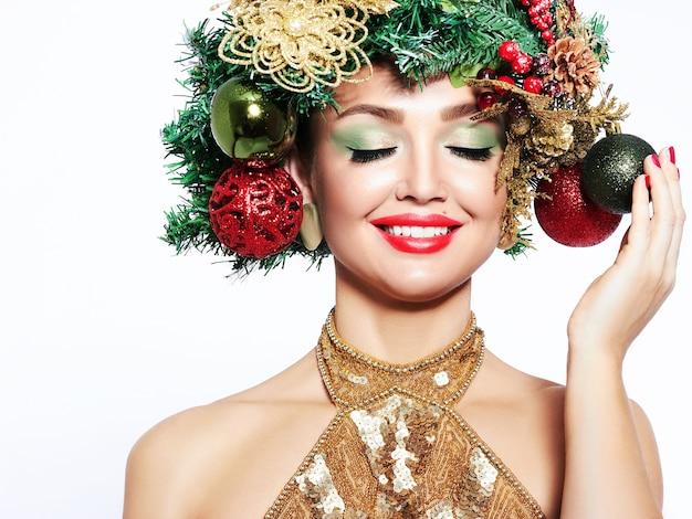 美しいクリスマスツリーのお祭りのヘアスタイルとメイク。