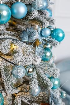 사진 스튜디오, 침실, 새해 장식의 겨울 내부에 있는 아름다운 크리스마스 트리. 파란 공 크리스마스 장난감입니다. 새해가 곧