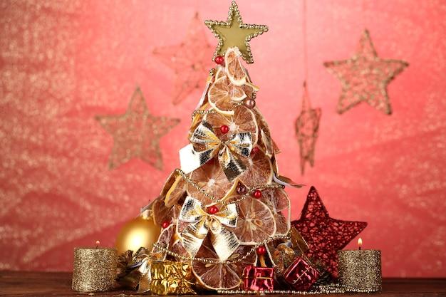 赤い背景に、装飾が施されたドライレモンの美しいクリスマスツリー