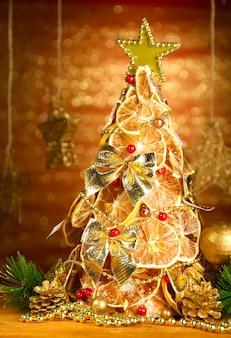 輝きの背景に、装飾が施されたドライレモンの美しいクリスマスツリー