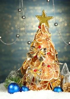 シャインブルーの背景に、装飾が施されたドライレモンの美しいクリスマスツリー