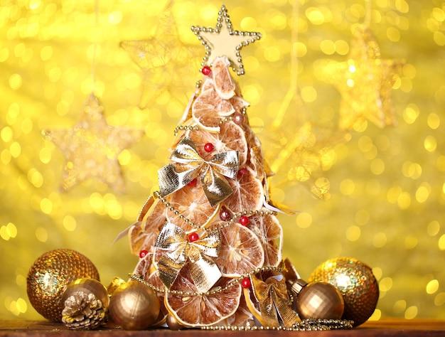 黄色の背景に、装飾が施されたドライレモンの美しいクリスマスツリー