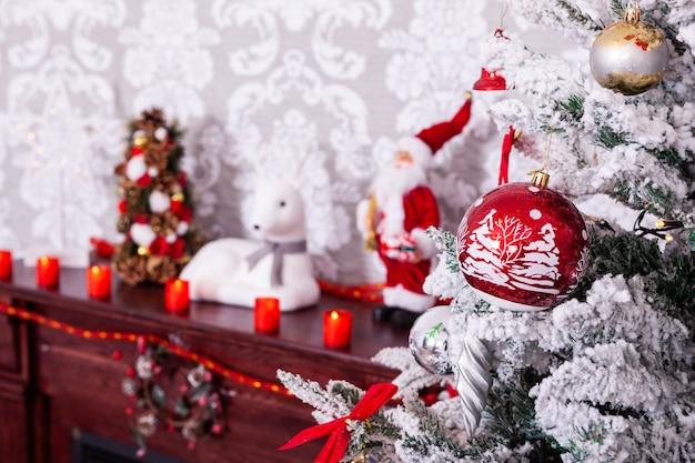 벽난로에 아름 다운 붉은 촛불과 함께 아름 다운 크리스마스 트리. 겨울이 왔습니다.