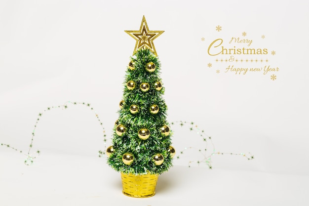 Beautiful christmas tree with gold baubles and garland lights white background
