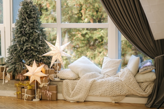 큰 창으로 선물 아름 다운 크리스마스 트리. 겨울이오고있다. 베개가 달린 격자 무늬