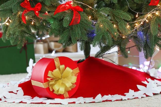 방에 치마와 선물 상자가 있는 아름다운 크리스마스 트리