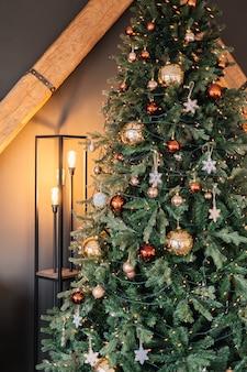 Красивая новогодняя елка с теплым светом напольной лампы.