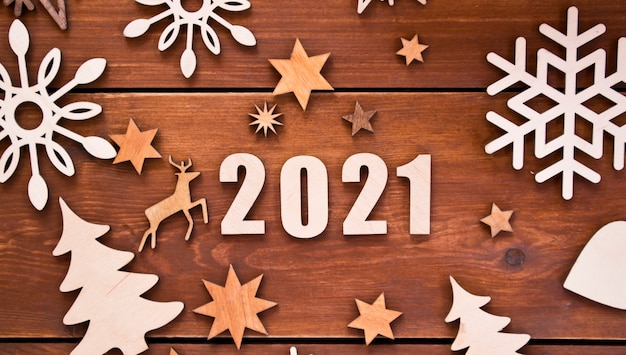 The beautiful christmas with a lot of small wooden decorations and wooden numbers 2021 on the wooden desk.